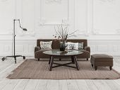 Simple living room seating area with brown sofa and table on a rug in a formal room with ornate whit poster