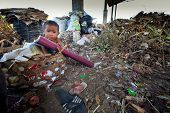 BALI, INDONESIA - APRIL 11: Unidentified child is sitting during his parents are working in a scavenging at the dump on April 11, 2012 on Bali. Bali daily produced 10,000 cubic meters of waste.