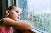 Little Sad Girl Pensive Looking Through The Window Glass With A Lot Of Raindrops. Sadness Childhood  poster