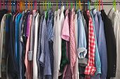 Close-up Of Hangers With Different Fashionable Clothes. Childrens Clothes Of Different Colors Are Hu poster