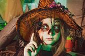 Kid Eyes With Skull Make Up. Little Witch. Funny Child Girl With Skeleton Costume Holding Skull And  poster