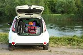 Car With Camping Equipment In Trunk On Riverbank. Space For Text poster
