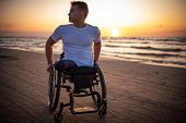Handicapped man in wheelchair and his girlfriend alone on a beach at sunset poster