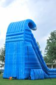 stock photo of inflatable slide  - A large inflatable slide with blower visable is set up for a crawfish dinner event - JPG