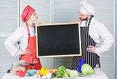 Teaching Different Cooking Techniques. Couple Of Man And Woman Holding Board In Cooking School. Mast poster