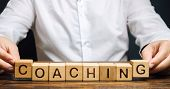 Wooden Blocks With The Word Coaching In The Hands Of A Man. Self Improvement. Achieving Goals Throug poster
