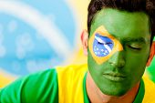 Man portrait with flag from Brazil painted on his face