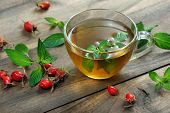 Cup Of Mint Tea On A Wooden Table. Mint Leaves, Rose Hips And Brewed Mint. Alternative Medicine. Col poster