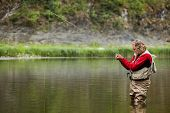 Fly Caster Angler Is Fishing In The Wild River Use Fly Casting Or Fly Fishing. poster