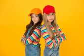 Fashion That Matches Their Conscious Style. Small Girls In Style Keeping Arms Crossed On Yellow Back poster