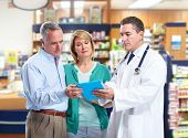 Pharmacist and a senior couple in pharmacy.