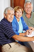 Portrait of three happy seniors sitting at table in a rest home