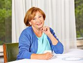 Portrait of a confident elderly woman with cup of coffee at the table