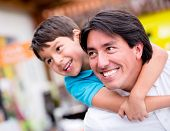 image of piggyback ride  - Happy father playing with his son and smiling - JPG