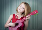 Young blonde girl dressed in red is playing ukulele.