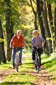 Senior-Mann und Frau trainieren mit Fahrrädern im freien, sie sind ein paar