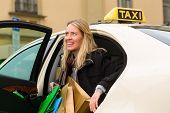 Junge Frau steigt aus der Taxi, sie hat ihr Ziel erreicht