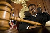 Portrait of African American judge with mallet on table in classroom