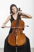 Beautiful young woman playing cello classical music instrument