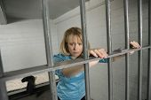 Upset businesswoman standing behind bars in jail