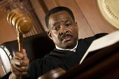 African American judge pounding mallet in courtroom