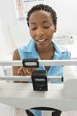 Happy African American woman adjusting scale of weighing machine
