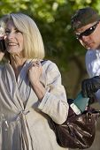 stock photo of unawares  - Thief pickpocketing wallet from senior woman - JPG