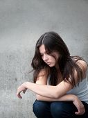 stock photo of sad eyes  - Outdoor portrait of a sad teenage girl looking thoughtful about troubles in front of a gray wall - JPG