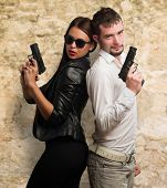 Young Couple Holding Gun against a stone wall