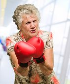 Angry Mature Woman Wearing Boxing Gloves, Indoors