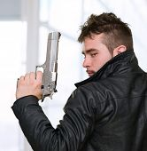 Portrait Of A Man Holding Gun against an abstract background