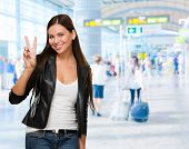 Pretty Young Woman Giving Victory Sign at the airport, indoor