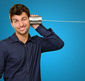 Young Man Listening From Tin Can Phone On Blue Background