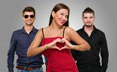 stock photo of dress-making  - Woman Standing In Front Of Men Making A Heart Shape Sign On Gray Background - JPG