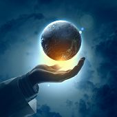 stock photo of longitude  - Hand of businessman holding earth planet against illustration background - JPG