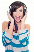 Young woman singing and listening music in headphones