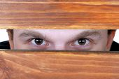 Man eyes looking through hole in wooden desk