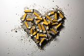 stock photo of smoker  - Love heart made of smoked cigarettes and ash - JPG