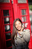 London woman taking on smartphone by red phone booth. Young casual female business woman having conv