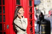 London business woman on smart phone by red phone booth. Communication concept with young multiracia