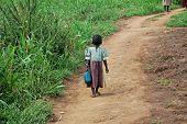 Ugandan Girl Carries Jerry Can On A Dirt Path