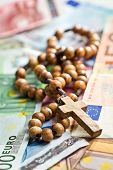 rosary beads on euro currency background