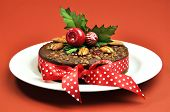 Christmas Fruit Cake Decorated With Nuts, Holly And A Bright And Cheerful Red Polka Dot Ribbon, On A