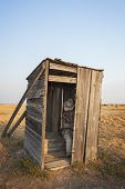 stock photo of outhouse  - Mannequin sitting in old wooden outhouse South Dakota - JPG