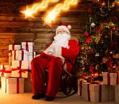 Santa Claus sitting on rocking chair in wooden home interior with gift boxes around him and two fall