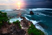 Sunset over rocky coast of Indian Ocean. Bali island, Indonesia