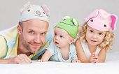 foto of baby frog  - happy dad with kids in funny hats lying on the bed - JPG