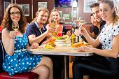 picture of diners  - Friends or couples eating fast food and drinking beer and wine in a American fast food diner - JPG