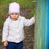 Brown Eyed Baby Girl In Pink Hat Opens Old Green Wooden Wicket