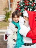 Santa Claus whispering in boy's ear in front of Christmas tree